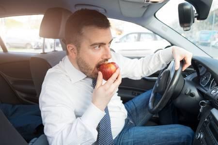 81052892-彼の車を運転してリンゴを食べる男.jpg